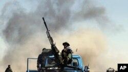 利比亚反政府武装在卡车上向亲卡扎菲的空袭战机射击