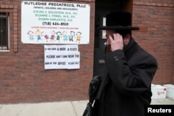 FILE PHOTO: A sign warning people of measles in the ultra-Orthodox Jewish community of Williamsburg in New York City, April 11, 2019.