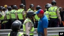 지난 18일 베네수엘라 카라카스의 국가선거본부 앞에서 경찰과 반정부 시위대가 실랑이를 벌이고 있다. (자료사진)