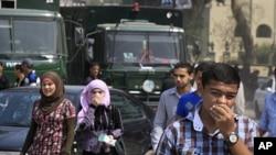 在开罗发生冲突的以色列使馆附近,行人周六掩住口鼻以免吸入催泪弹释放的瓦斯