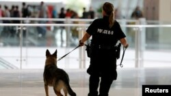 FILE - A San Diego Harbor Police K-9 officer patrols Lindbergh Field airport in San Diego, California, July 1, 2016.