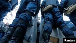 Polisi anti huru-hara Ukraina berdiri di belakang tameng saat memblokir jalan di Kiev (14/12).