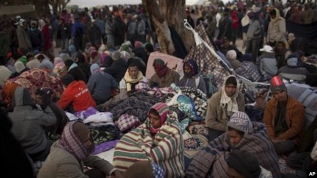 Men, who worked in Libya and fled the unrest in the country, wait for buses to be repatriated in a refugee camp at the Tunisia-Libyan border, in Ras Ajdir, Tunisia, March 10, 2011