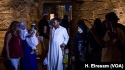 Des touristes posent devant le temple de Louxor, à Luxor, Egypte, le 9 septembre 2017. (H. Elrasam/VOA)