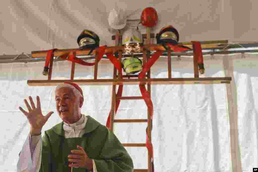 A cross made with ladders and firefighter helmets is placed inside a tent during a Mass celebrated by Bishop Giovanni D'Ercole, in Arquata Del Tronto, near Amatrice, central Italy. The tent was set up as a temporary shelter for the earthquake survivors.