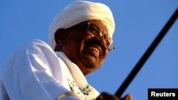 Sudanese President Omar al-Bashir surveys a rally with Sufi supporters in Hajj Yusuf at Khartoum district, Dec. 27, 2014.