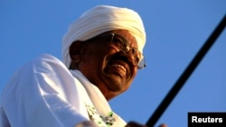 FILE: Sudanese President Omar al-Bashir surveys a rally with Sufi supporters in Hajj Yusuf at Khartoum district, Dec. 27, 2014.