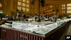 In this Wednesday, Feb. 27, 2013, Cambodian vendors sit in their jewelry booths in the Central Market (Phsar Thum They) in Phnom Penh, Cambodia. Beneath a lemon-yellow art deco dome, the Central Market offers miles of no-strings-attached window-shopping.
