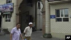维吾尔族人走过中国新疆维吾尔族自治区乌鲁木齐市的一座穆斯林清真寺。(资料照片)