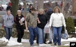 Des parents et élèves passent devant l'Ecole primaire de Chardon, proche du lycée où a eu lieu la fusillade (27 fév. 2012)