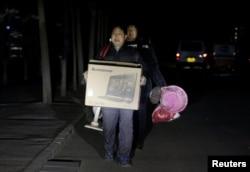 北京的外来务工人员手里提着有限的个人物品被连夜赶出他们在北京通州六环外的住所。(2017年11月23日)
