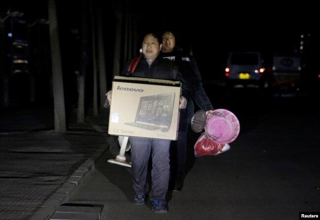 北京的外來務工人員手裡提著有限的個人物品被連夜趕出他們在北京通州六環外的住所。 (2017年11月23日)