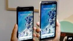 Seorang perempuan memegang ponsel Google Google Pixel 2 phone, kiri, di sebelah Pixel 2 XL di acara Google di SFJAZZ Center di San Francisco, 4 Oktober 2017.