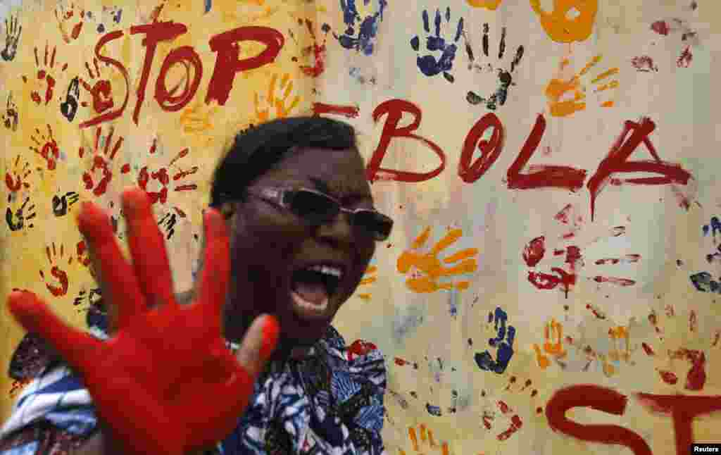 A teacher reacts after adding paint to a canvas following a performance by actors during an awareness campaign against Ebola at Anono school, in Abidjan, Ivory Coast, Sept. 25, 2014.
