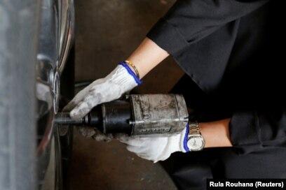 Huda al-Matroushisedang memperbaiki roda mobil di bengkelnya di Sharjah, Uni Emirat Arab, 21 April 2021. (Foto: Rula Rouhana/Reuters)