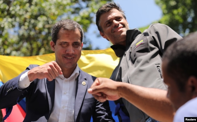 Venezuelan opposition leader Juan Guaido, left, pumps fists with a supporter as fellow opposition leader Leopoldo Lopez looks on in Caracas, April 30, 2019.