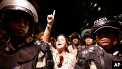Mitzy Capriles de Ledezma chants for the release of her husband, Mayor Antonio Ledezma, as national police officers guard intelligence service police headquarters in Caracas, Venezuela, Feb. 19, 2015.