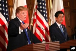 FILE - President Donald Trump, left, speaks as Japanese Prime Minister Shinzo Abe looks on during a joint news conference at the Akasaka Palace in Tokyo, Nov. 6, 2017.