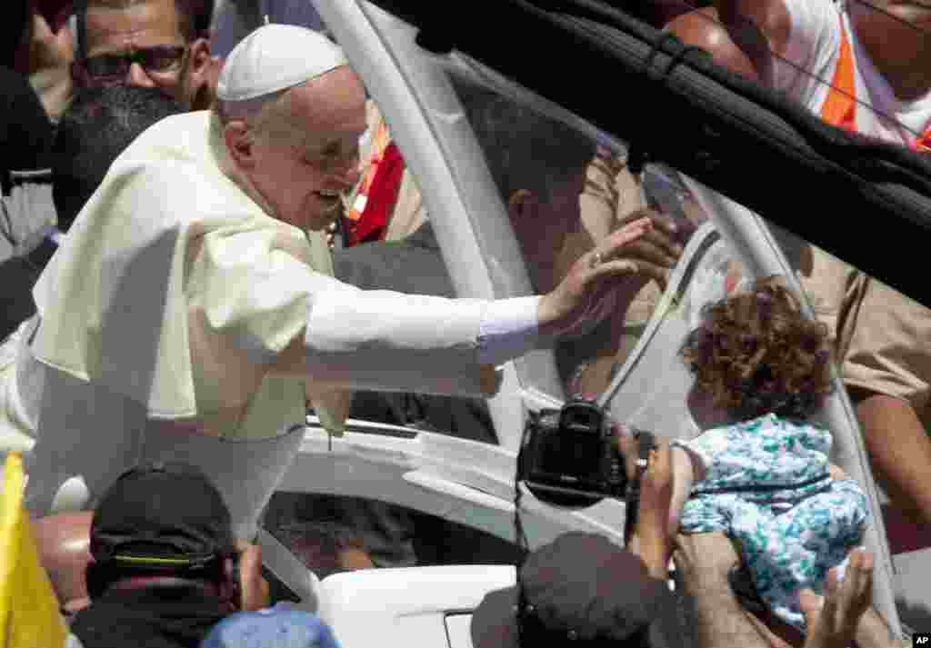 Pope Francis reaches to a girl after a mass in Bethlehem.