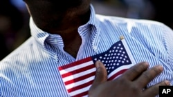 A candidate for citizenship holds the American flag at the start of a naturalization ceremony in Atlanta, Sept. 16, 2016.