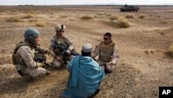 Dua marinir AS ditemani seorang penerjemah Afghan berbincang dengan seorang warga Afghanistan di Provinsi Helmand, Afghanistan, 11 Desember 2009. (Foto: AP)