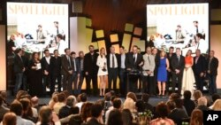 "Michael Sugar, center, and the cast and crew of ""Spotlight"" accept the award for best feature at the Film Independent Spirit Awards in Santa Monica, Calif., , Feb. 27, 2016."