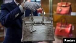 FILE - An employee holds an Hermes diamond and Himalayan Nilo Crocodile Birkin handbag at Heritage Auctions offices in Beverly Hills, California, Sept. 22, 2014.