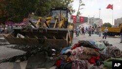 工作人員在清理伊斯坦布爾一個廣場抗議人士遺留下來的雜物。