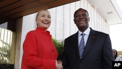 U.S. Secretary of State Hillary Clinton and Ivory Coast President Alassane Dramane Ouattara shake hands after holding a joint news conference at the Presidency in Abidjan, January 17, 2012.