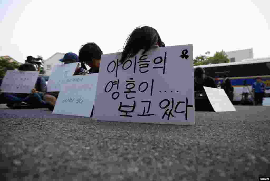 Family members of victims onboard sunken ferry Sewol sit in front of a building in which crew members are detained, after attending a hearing at the local court in Gwangju, South Korea, June 10, 2014.