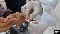 Seorang petugas mengambil sampel darah dalam tes cepat massal Covid-19, di Jakarta, 23 April 2020. (Foto: AFP)