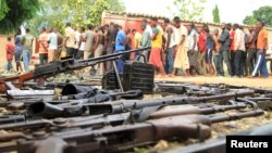 Suspected fighters are paraded before the media by Burundian police near a recovered cache of weapons after clashes in the capital Bujumbura, Burundi, Dec. 12, 2015.