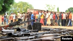 FILE - Suspected fighters are paraded before the media by Burundian police near a recovered cache of weapons after clashes in the capital Bujumbura, Burundi, Dec. 12, 2015.