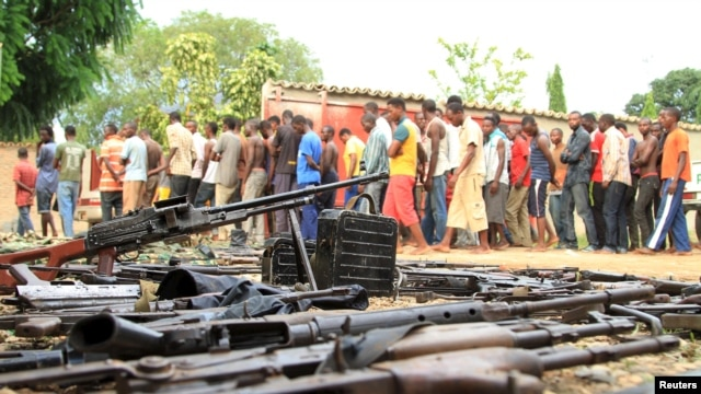 FILE - Suspected fighters and recovered weapons are shown in Bujumbura, Burundi, Dec. 12, 2015. Burundian President Pierre Nkurunziza's senior adviser says such images of unrest are propaganda intended to tarnish Burundi.