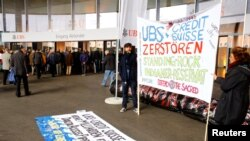 "FILE - Protesters display a banner to protest against the financing of the Dakota Access oil pipeline by Swiss banks UBS and Credit Suisse as participants arrive ahead of the annual shareholder meeting of Swiss bank UBS in Basel, Switzerland, May 4, 2017. The banner reads ""UBS + Credit Suisse destroy the Standing Rock Native American reserve."""