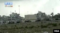 Pasukan Suriah dengan tank-tank tampak melakukan penyerbuan ke kota pantai Latakia hari Sabtu (13/8).