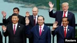 FILE- Leaders pose during the photo session at the APEC Summit in Danang, Vietnam, Nov. 11, 2017. Front left, China's President Xi Jinping. Rear center and right, Russia's President Vladimir Putin, U.S. President Donald Trump.