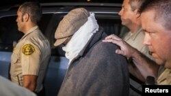 Nakoula Basseley Nakoula (ditutup mukanya) dikawal oleh beberapa Polisi Los Angeles dari rumahnya di kota Cerritos, California (15/9). Nakoula adalah pria yang diduga memproduksi film 'Innocence of Muslims'.