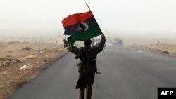 Повстанец с королевским ливийским флагом во время обстрела правительственными войсками портового города Рас-Лануф.