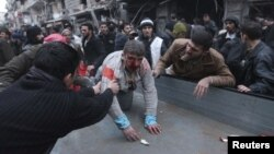 People help a wounded person after a missile hit Aleppo's al-Mashhad district, Syria, January 7, 2013.
