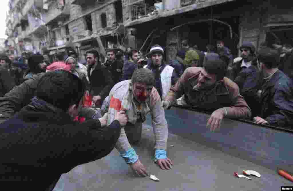 Des personnes adaint un blessé après un tir de missile à Alep