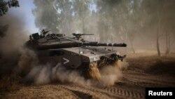 Tank Israel melakukan manuver setelah gencatan senjata lima jam berakhir dekat perbatasan Gaza (17/7).