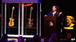 "FILE - Guernsey's auctioneer Joanne Grant conducts bidding on guitars previously owned by the late Jerry Garcia during an auction, May 8, 2002, at Studio 54 in New York. The guitar named ""Wolf,"" left, sold for over $700,000."