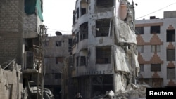 FILE - A man rides a bicycle past damaged buildings in the Douma neighborhood of Damascus, Nov. 26, 2015.