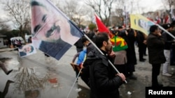 FILE - Demonstrators wave flags with the image of imprisoned Kurdish rebel leader Abdullah Ocalan during a rally in Istanbul, Feb. 15, 2015. Ocalan called on followers to agree to lay down their arms.