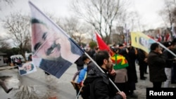 FILE - Demonstrators wave flags with the image of imprisoned Kurdish rebel leader Abdullah Ocalan during a rally in Istanbul, Feb. 15, 2015.