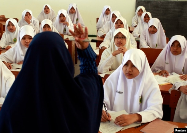 FILE - A teacher gestures during an Islam personality class during the holy month of Ramadan at the Al-Mukmin Islamic boarding school in Solo, Indonesia Central Java province, Aug. 2, 2011.