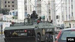 Seorang tentara mengendarai kendaraan lapis baja di Ettadhamoun, Tunisia bagian barat, di mana kerusuhan dilaporkan.