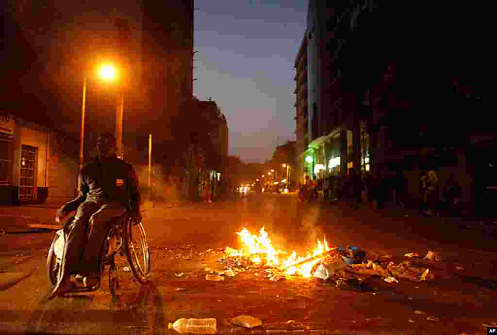 A man passes by a street fire lit by anti-government protesters on a central boulevard in Dakar, Senegal, Feb. 23, 2012. (AP)