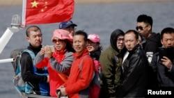 中国游客在靠近辽宁丹东市的鸭绿江上乘船观光。(2017年4月2日)